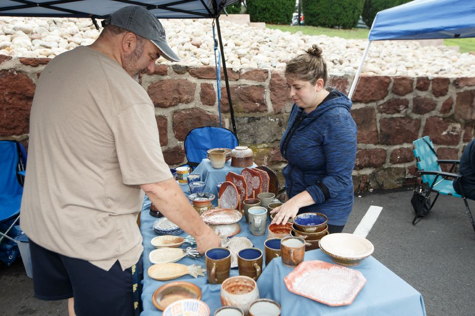 Many Ronert of Newington shows her work to Arnold Berman of Glastonbury Sunday during a Summer Sidewalk Sale at Southington Community Cultural Arts Center in Southington July 22, 2018 | Justin Weekes / Special to the Record-Journal