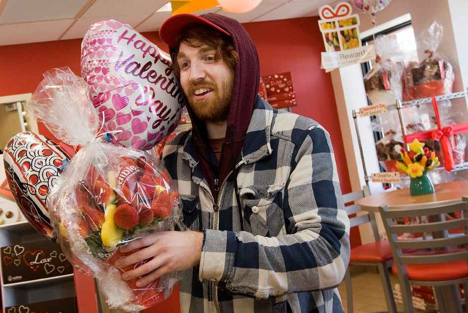 Eric Fisk, of Meriden, a produce and prep worker, carries an order to a delivery truck at Edible Arrangements in Wallingford, Monday, February 13, 2017. | Dave Zajac, Record-Journal
