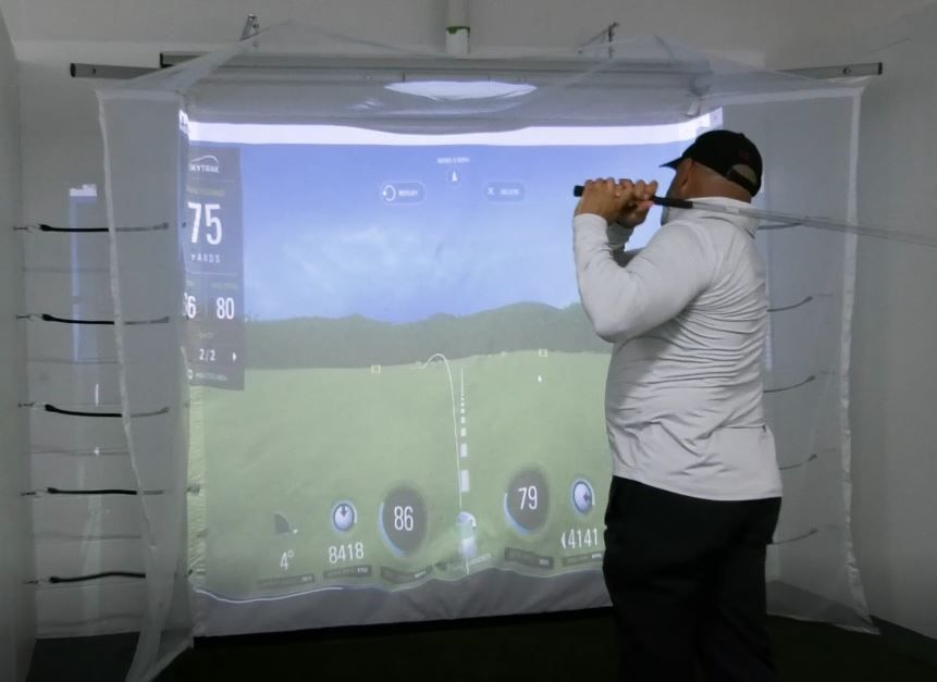 Left: Willie Feliciano, sponsor of the new golf simulator, tries it out Friday  at the Meriden YMCA, 110 W. Main St. in Meriden. Right: Feliciano and sport director Justin Ferreira set up the program. Photos by Ashley Kus, Record-Journal