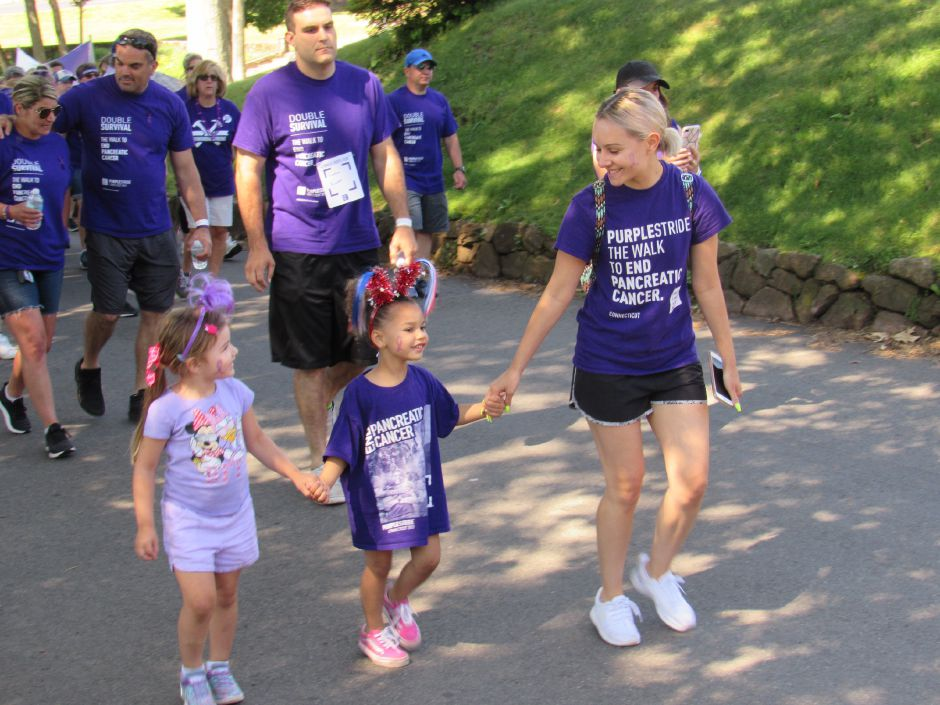 Ashley Mitchell walks with Aria, 5, and Iris, 5, in the Pancreatic Cancer Action Network's the Purple Stride walk in Hubbard Park. Saturday, June 15, 2019. | Jeniece Roman, Record-Journal