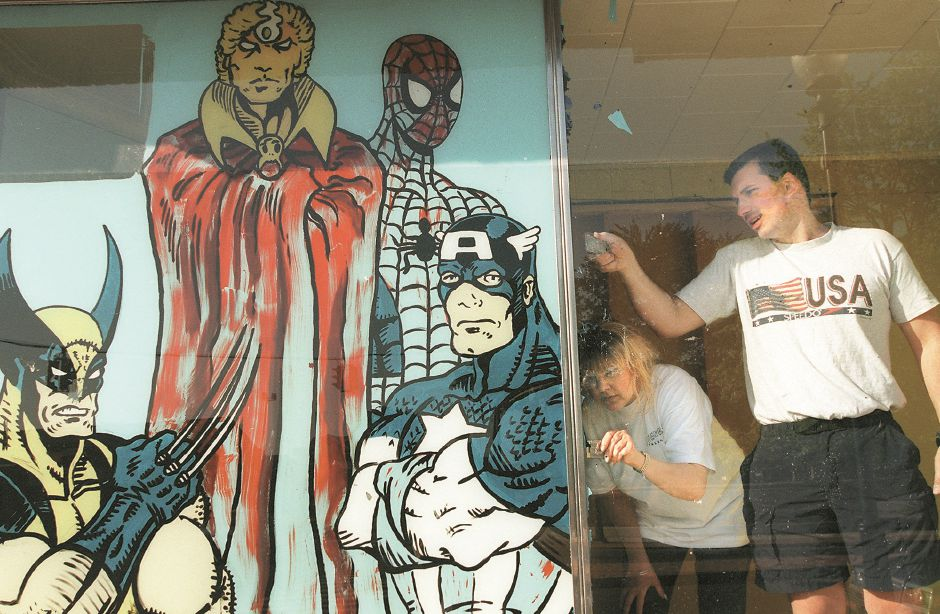 RJ file photo - Lori Yetke and Tom Fedora scrape the superheroes from the windows of the former Showcase Comics and Cards at Center and North Colony streets in Wallingford to make way for their own shops Nikori and Scandals salon and boutique, May 13, 1998.