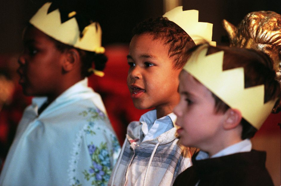 RJ file photo - Manny Williams, 5, center, Jennie Abutu, 5, left and Patrick Petit, 5, all kindergartners at St. Joseph School, sing with classmates during a performance in the church Jan. 6, 1999.
