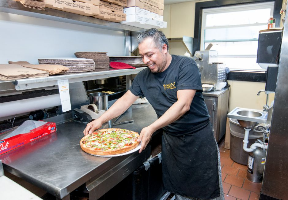 Juan Carlos, of Plainville, prepares to box up a pizza at Max Pizza 6 in Southington. The restaurant held its grand opening Thursday, April 20, 2018. | Devin Leith-Yessian/Record-Journal