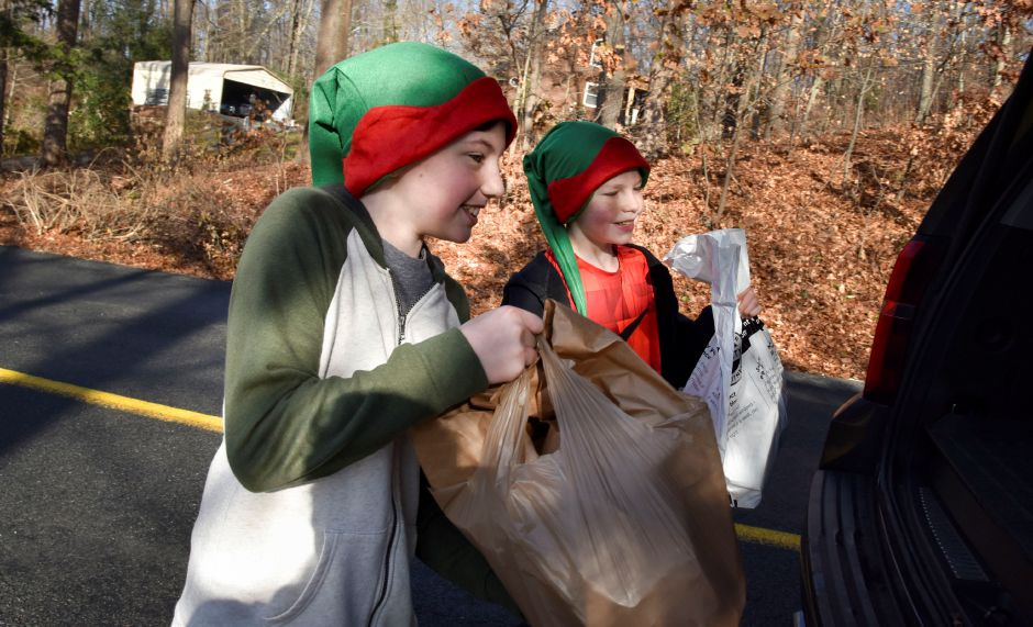 Joe Bugai (left) and Justin Rowe (right) load up food donations that they collected while going door-to-door during the 13th annual Community Round-up in Durham and Middlefield on Saturday, Dec. 1, 2018. The event collected more than 13,000 food items and about $3,500 to go to Durham and Middlefield Social Services, and Amazing Grace in Middletown. | Bailey Wright, Record-Journal