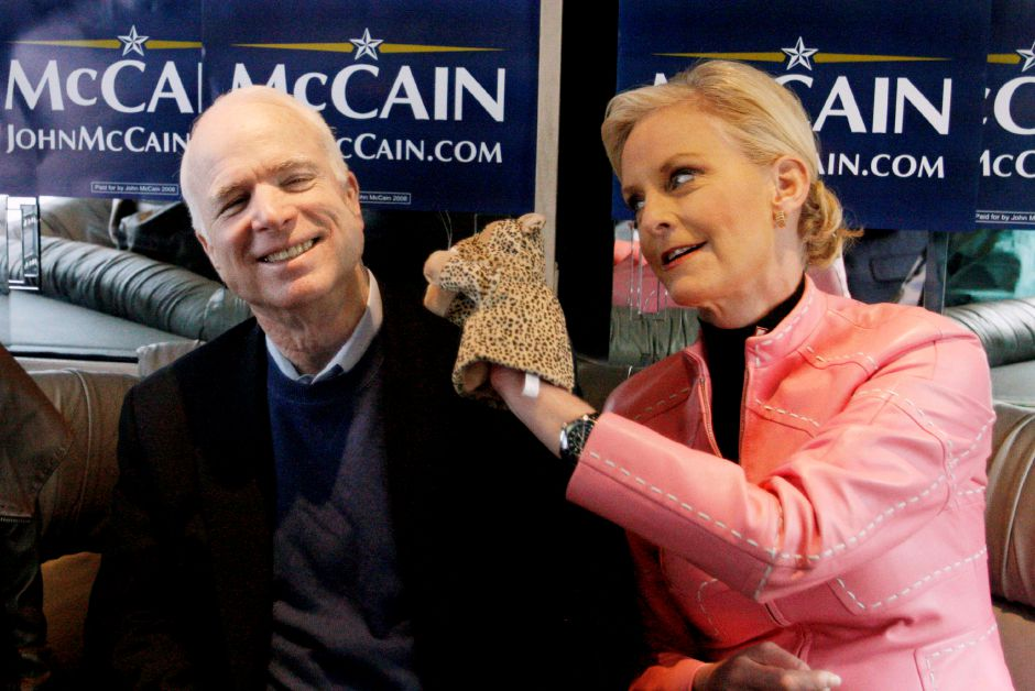 "FILE - In this Jan. 19, 2008 file photo, Cindy McCain, wife of Republican presidential hopeful Sen. John McCain, R-Ariz., uses a cheetah hand puppet to make her husband laugh as they ride the ""Straight Talk Express"" campaign bus to a polling station on the day of South Carolina"