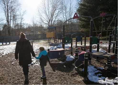 Jennifer Reilly, of Wallingford, walks with son Collin, 7, at the Doolittle Park playground in Wallingford, Thursday, March 23, 2017. Collin became permanently blind at six months old after doctors performed surgery to remove cancer tissue from his brain, which they warned could happen prior to surgery. A fundraiser for Collin is being held at Serenity Salon and Day Spa, 118 Center Street, this Sunday from 10 a.m. to 3 pm. | Dave Zajac, Record-Journal