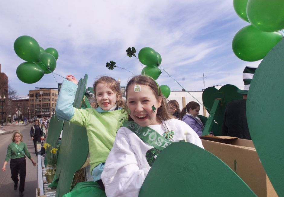 Lila Purvis, 8, of Cheshire, left, and Sarah Marnalse, 12, of Wallingford, right, ride on the back of a truck decorated with shamrocks down West Main Street, in Meriden, Conn., during the St. Patrick