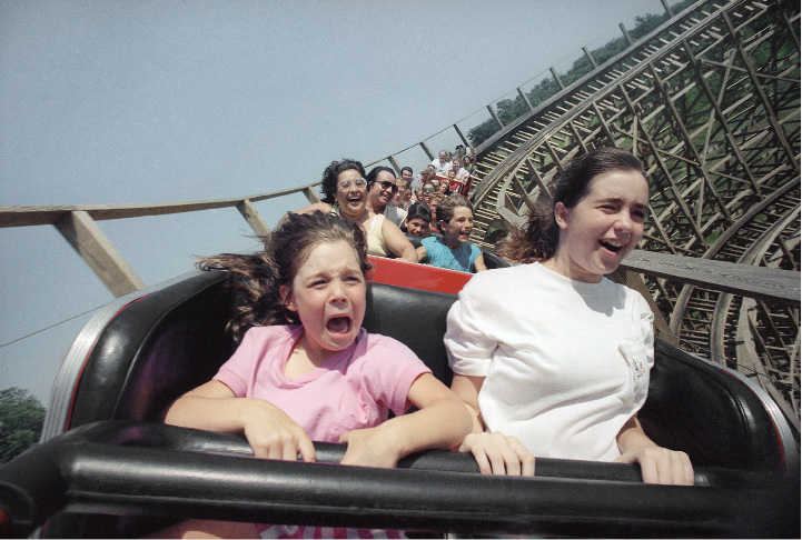 Two unidentified girls react to a front seat view of the Timber Wolf wooden roller coaster at Worlds of Fun in Kansas City, July 16, 1990. It was designed by Curtis Summers who has created 29 of these structures which provide a rougher ride than the steel-framed roller coasters. (AP Photo/Cliff Schiappa)