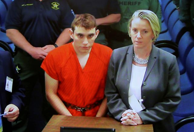 A video monitor shows school shooting suspect Nikolas Cruz, left, making an appearance before Judge Kim Theresa Mollica in Broward County Court, Thursday,  in Fort Lauderdale, Fla.