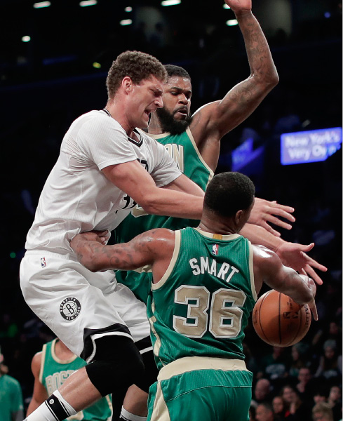 Brooklyn Nets center Brook Lopez (11) is stripped of the ball as Boston Celtics guard Marcus Smart (36) and forward Amir Johnson (90) defend during the first quarter of an NBA basketball game, Friday, March 17, 2017, in New York. (AP Photo/Julie Jacobson)
