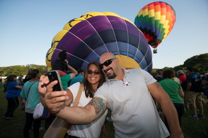 "Rick and Rebee Mercede of Oxford stop to take a ""selfie"" with hot air balloons Friday during the Plainville Fire Company 33rd Annual Hot Air Balloon Festival at Norton Park in Plainville Aug. 25, 2017 