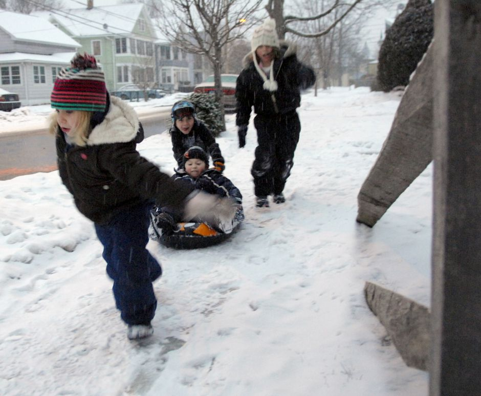 WALLINGFORD, Connecticut - Saturday, January 10, 2009 - Robby Nolan, 4, sitting in a sled, is pulled down the snow-covered sidewalk by Taylor Deroy, 8, and helping push is Taylor