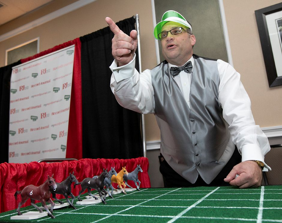 Quinnipiac Chamber of Commerce Business Development Executive Gary Ciarleglio summons players for a horse race game during the casino-themed Quinnipiac Chamber of Commerce Annual Business Showcase at the Best Western in North Haven, Thurs., Apr. 4, 2019. Dave Zajac, Record-Journal