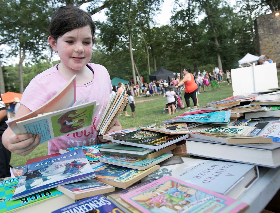 Sophia McMahon, 9, of Meriden, picks up a bundle of free books while at Center Congregational Church