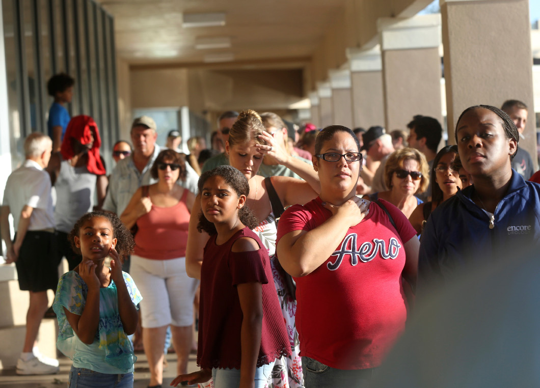 People line up for the announced opening of a Publix grocery store, the first food chain to re-open in Naples, in the aftermath of Hurricane Irma in Naples, Fla., Tuesday, Sept. 12, 2017. The store could not open its doors on time because they were trying to get the cash registers online. (AP Photo/Gerald Herbert)