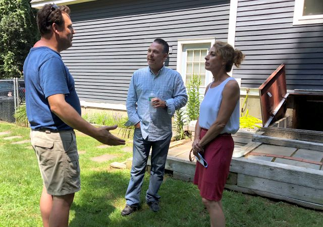 Homeowner Tim Hein, center, speaks with Sean, left, and Jenny Cassells outside his home, Monday, Aug. 6, 2018, in Willington, Conn., after the latest political candidate visited to see how foundation is crumbling and cracking. The Cassells
