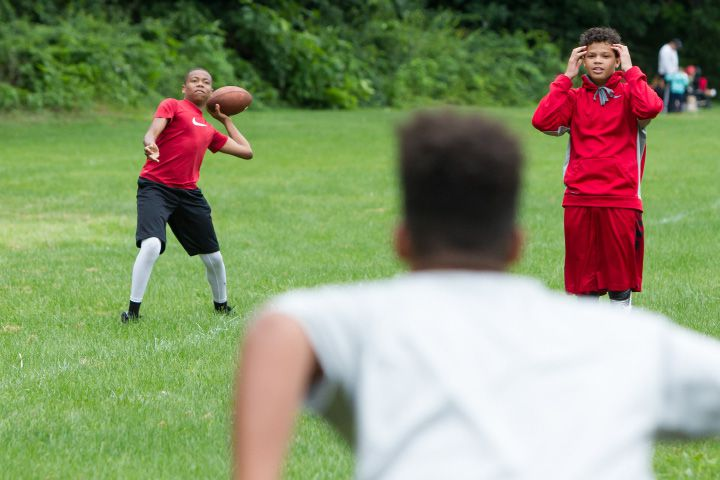 Isaiah Conner, 13, of Meriden, left throws a pass Monday during the Meriden Raiders youth football opening day at Washington Park in Meriden Jul. 24, 2017 | Justin Weekes / For the Record-Journal