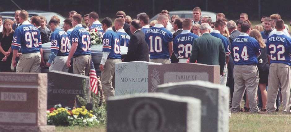 The Southington High School football team, wearing their jerseys together with family and friends of the late 16-year-old Matthew J. Henne carry the casket during funeral services at Immaculate Conception Church. Henne died Saturday , August 21, at Hartford Hospital after sustaining injuries in an accident at Lake Compounce.