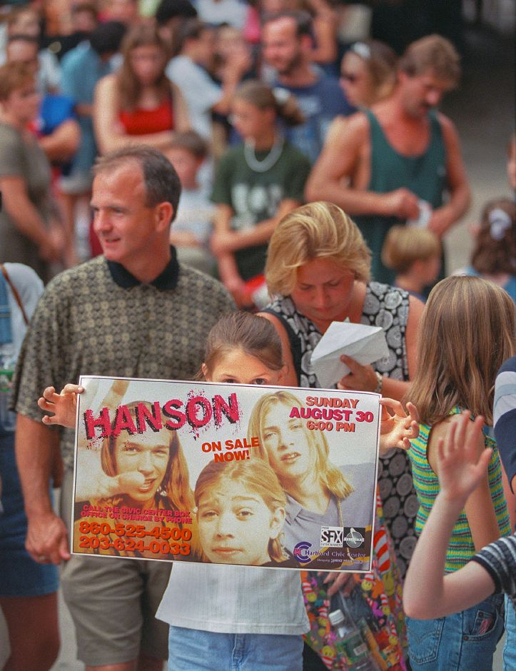 RJ file photo - Jessica Verbanic, 11, of Ridgefield, holds up her fan poster as she waits with numerous other young girls and their parents for the Hanson concert in Harford, Sept. 1998.