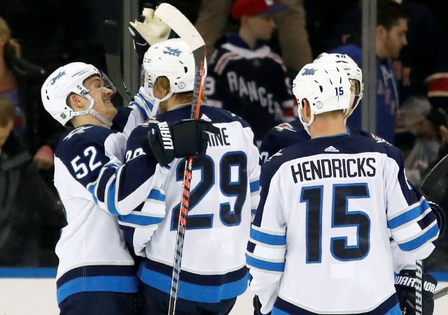 Winnipeg Jets center Jack Roslovic (52) celebrates with Jets right wing Patrik Laine (29) of Finland who had a hat trick after the Jets shut out the New York Rangers 3-0 in an NHL hockey game in New York, Tuesday, March 6, 2018. Jets center Matt Hendricks (15) looks on. (AP Photo/Kathy Willens)