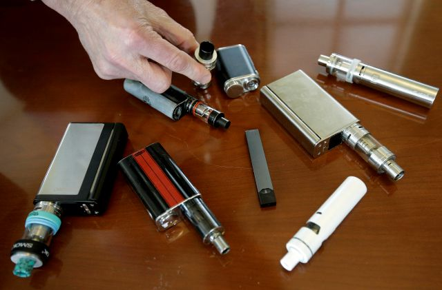 In this Tuesday, April 10, 2018 photo Marshfield High School Principal Robert Keuther displays vaping devices that were confiscated from students in such places as restrooms or hallways at the school in Marshfield, Mass. Health and education officials across the country are raising alarms over wide underage use of e-cigarettes and other vaping products.The devices heat liquid into an inhalable vapor that