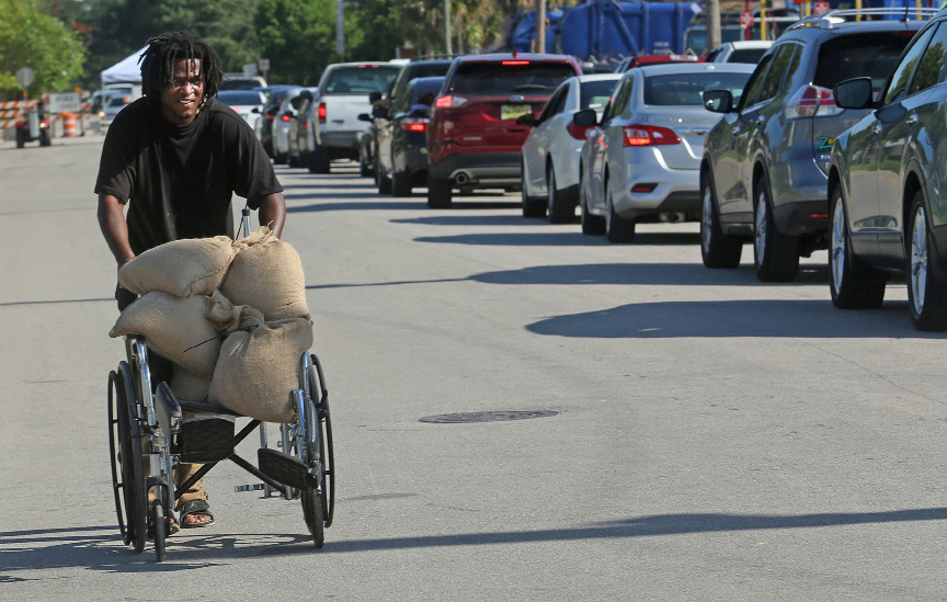 Tyrone Tomlinson, 27, of Orlando, uses a family wheelchair to ferry sandbags to be used on the front porch of their family home in Orlando, Fla., Thursday, Sept. 7, 2017, as residents prepare for Hurricane Irma. Long lines of vehicles waited for hours to get a 10 sand bag limit at the City of Orlando Public Works. (Red Huber/Orlando Sentinel via AP)