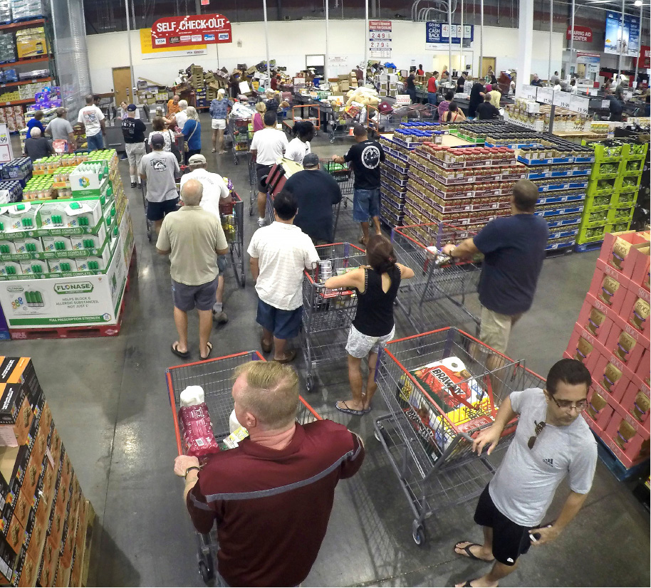 Shoppers wait in line to checkout during preparations for the anticipated arrival of Hurricane Irma, Wednesday, Sept. 6, 2017  in Altamonte Springs, Fla.  Irma roared into the Caribbean with record force early Wednesday, its 185-mph winds shaking homes and flooding buildings on a chain of small islands along a path toward Puerto Rico, Cuba and Hispaniola and a possible direct hit on densely populated South Florida.  (Joe Burbank/Orlando Sentinel via AP)
