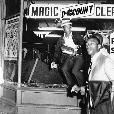 A black youth jumps out a smashed window of a dry cleaning establishment in area where rioters smashed windows, looted stores and attacked police in Philadelphia