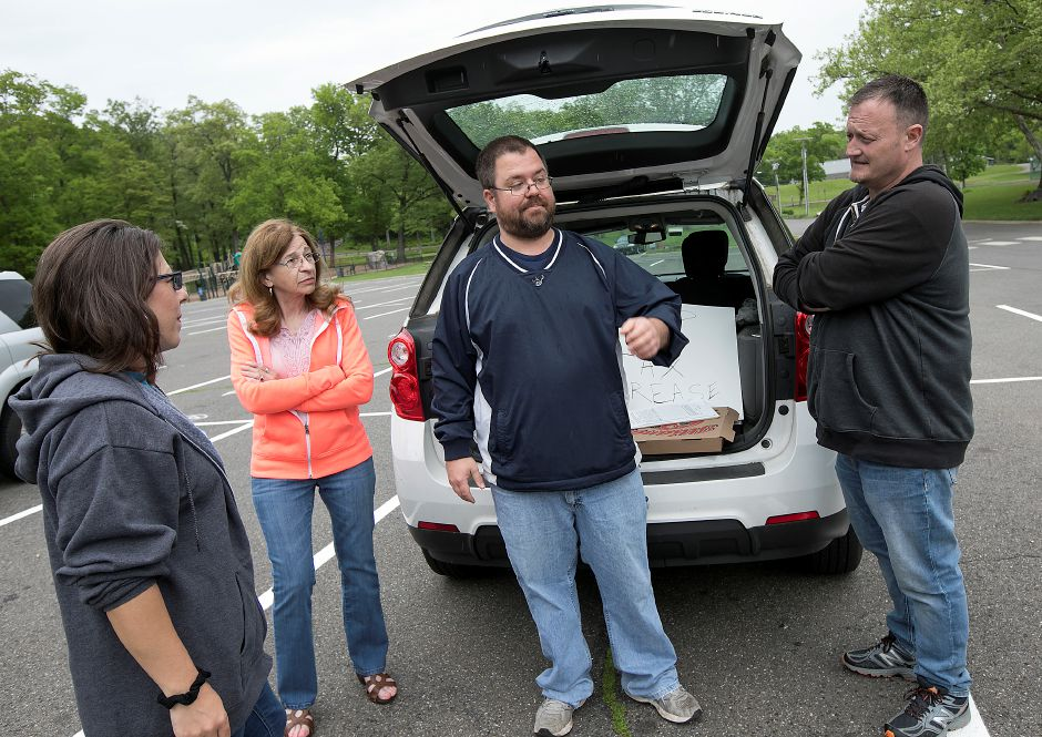 FILE PHOTO: Michael Carabetta, of Meriden, center, heads a petition against the city budget with, left to right, Sharon Milano, Patti Hall and Sean McDonald, all of Meriden, at Hubbard Park in Meriden, Tuesday, May 22, 2018. The City Council adopted a 198.1 million spending plan for the upcoming 2018-19 fiscal year. Dave Zajac, Record-Journal