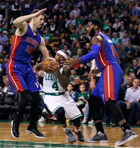 Boston Celtics guard Isaiah Thomas (4) threads between Detroit Pistons forward Jon Leuer (30) and center Andre Drummond, right, on a drive to the basket during the first quarter of an NBA basketball game in Boston, Wednesday, Nov. 30, 2016. (AP Photo/Charles Krupa)