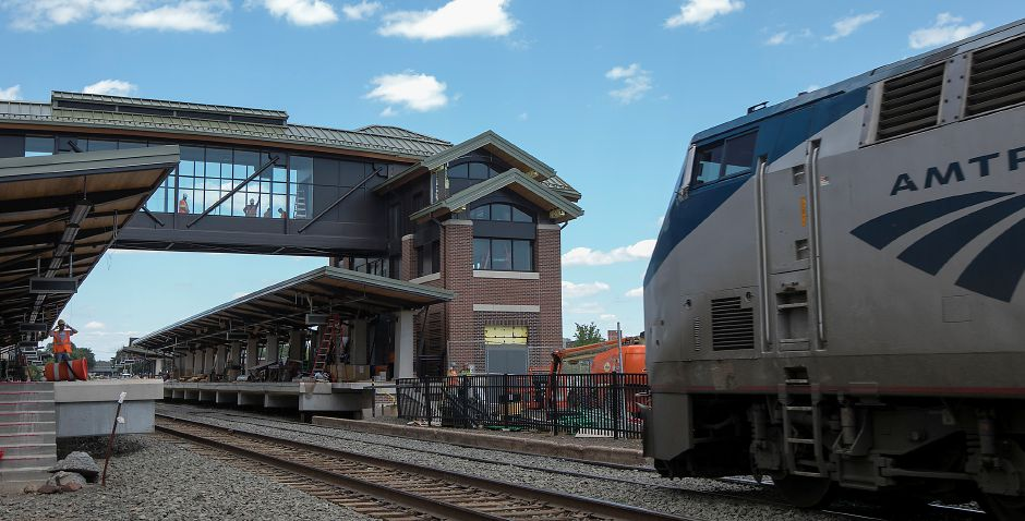 Work crews pause as an Amtrak train slowly approaches the Meriden Train Station under construction on State Street in Meriden, Wednesday, July 5, 2017. | Dave Zajac, Record-Journal