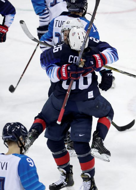 Kendall Coyne (26), of the United States, jumps on Hilary Knight (21) to celebrate after Knight scores a goal against Finland during the second period of the semifinal round of the women