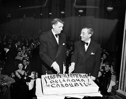 "Oscar Hammerstein II, left, and Richard Rodgers cut a cake in celebration of the first and third birthdays of their shows ""Carousel"" and ""Oklahoma"" at a Theater Guild reception in New York City on April 21, 1946. The occasion also marks the 27th birthday of the Guild. (AP Photo)"