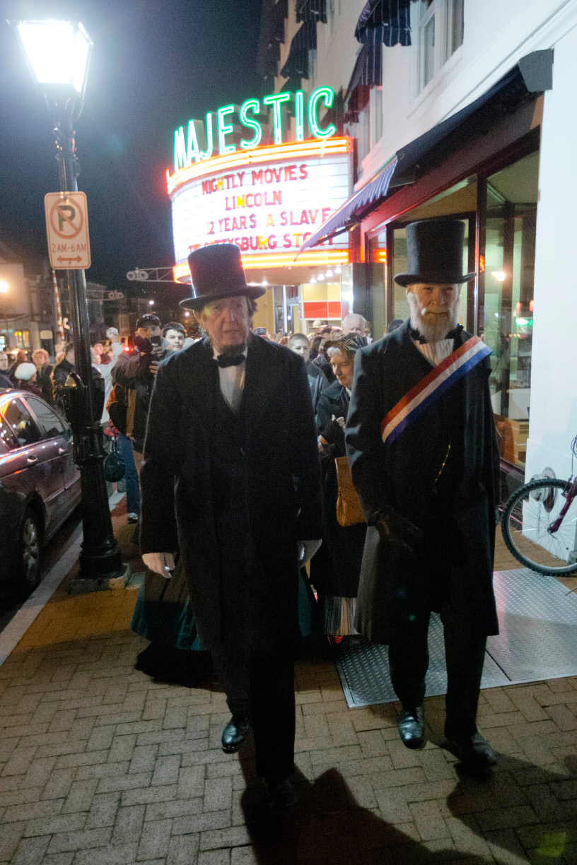 President Abraham Lincoln, portrayed by presenter Robert Costello, left, accompanied by David Wills, portrayed by presenter Joe Mieczkowski, walks past a theater marquee with Lincoln on it, Monday, Nov. 18, 2013, at the Gettysburg Train Station in Gettysburg, Pa. Tuesday, Nov. 19, marks the 150th anniversary of Lincoln