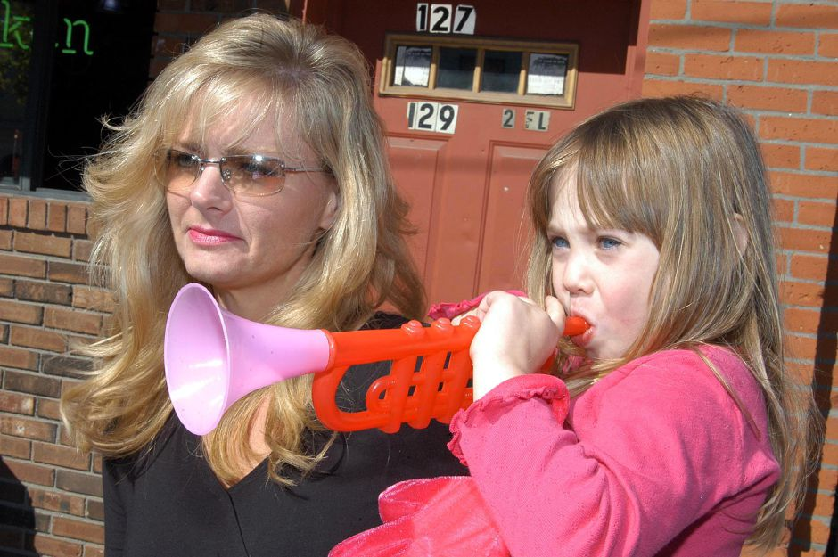 Jessica Kroeber blows her horn for the paraders as her mom, Jacy, looks on during the annual Apple Harvest Festival held Sunday in Southington.