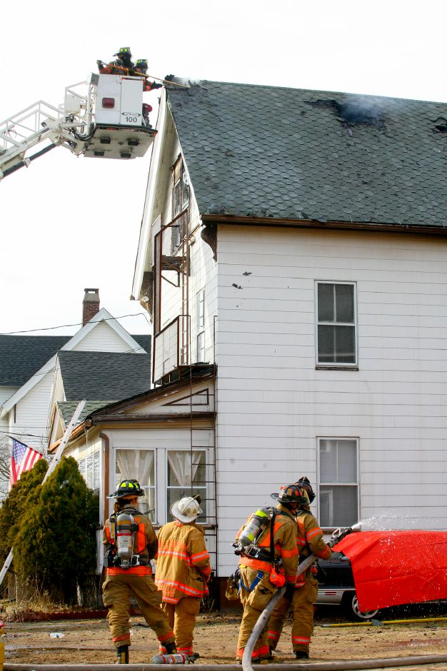 Wallingford Fire Fighters vent the roof of a Wallace Row home which caught fire while others stand by with a water hose in hand, Tuesday, March 2, 2010.