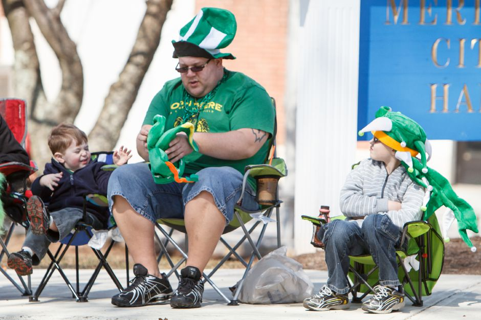 Trevor McMorran 2 waits for Dean McMorran of Meriden to fix his parade hat with Kaleb McMorran 7 during the St. Patrick