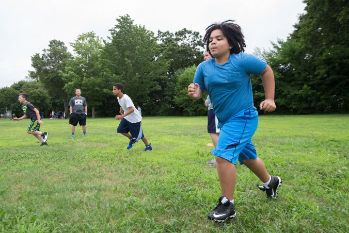 Dominic Wheeler, 12, of Meriden, warms up with his 12U teammates Monday during the Meriden Raiders youth football opening day at Washington Park in Meriden Jul. 24, 2017 | Justin Weekes / For the Record-Journal
