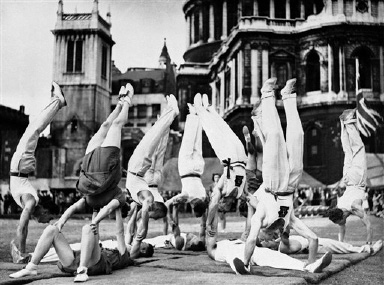 "Girls and men of the London Fire Forces form a pyramid in a fitting display of their physical fitness, as Londoners recently enjoyed all the fun of the Bank Holidays Fair on the blitzed site in the shadow of St. Paul's Cathedral in London on August 22, 1943. One of the chief attractions was an all-star cabaret show, including Tessie O'Shea, Patricia Burke, Robert Morley, David Miller and the ""Three Girl Friends."" (AP Photo)"