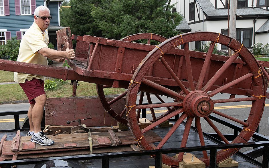 Wayne Mason, a Cook family descendant from Houston, Texas, installs the front panel of an ox cart his family donated to the Wallingford Historical Society. The ox cart, built in Wallingford in the 1850s, will be displayed at the Historical Society in a few months.