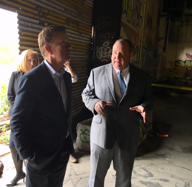 Gov. Ned Lamont listens to a pitch by Mayor Neil O'Leary in the abandoned Anamet factory. Behind them is Tamar Kotelchuck of the Boston Fed. | Mark Pazniokas, CT Mirror