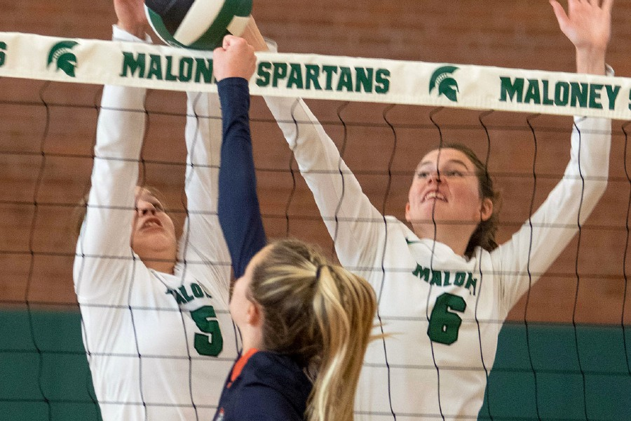 Maloney's Dasia Mongillo, left, and Elizabeth Barton block Lyman Hall's Hailey Bruneau during a volleyball match at Maloney High School on Monday. Maloney won 3-2. See more photos online at myrecordjournal.com/sports Aaron Flaum, Rcord-Journal