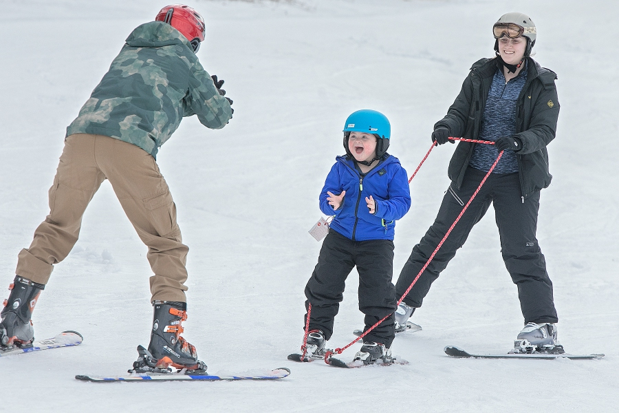 Ryan Yager, 7, of Brookfield, skis down the beginner hill with assistance from Quinnipiac University student Rachael Emond, right, and volunteer Brian Pawlow, of Bristol, left, during Skiers Unlimited at Mount Southington on Friday. Dave Zajac, Record-Journal