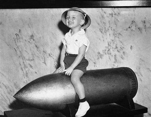 Two-year old James Dean Strachman appears to ride a 500-lb., 12-inch projectile in Galveston, Tex., Oct. 25, 1942. The historic cannon shell was used by Admiral Dewey