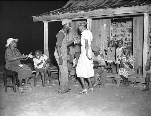 After a long day of picking cotton, people enjoy music and dance at night outside a cabin on Aug. 31, 1937.  These workers are among 700 blacks living on the Will Howard Smith plantation near Prattville, Alabama.  (AP Photo)