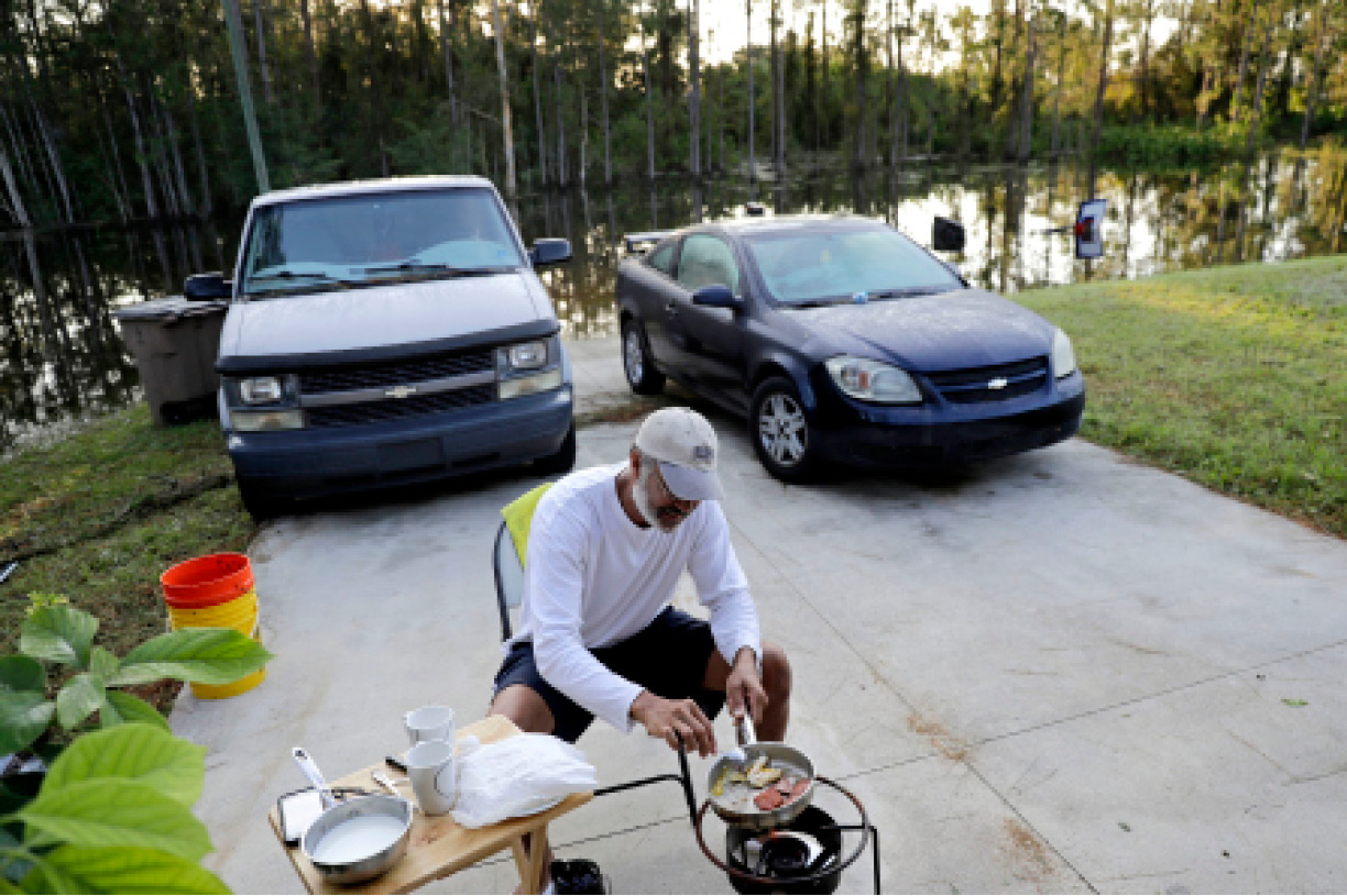 Cesar De La Cruz makes breakfast on a propane stove in his driveway as his neighborhood is flooded from Hurricane Irma in Fort Myers, Fla., Tuesday, Sept. 12, 2017. Millions statewide remained without power and officials warned it could take weeks for electricity to be restored to everyone. (AP Photo/David Goldman)