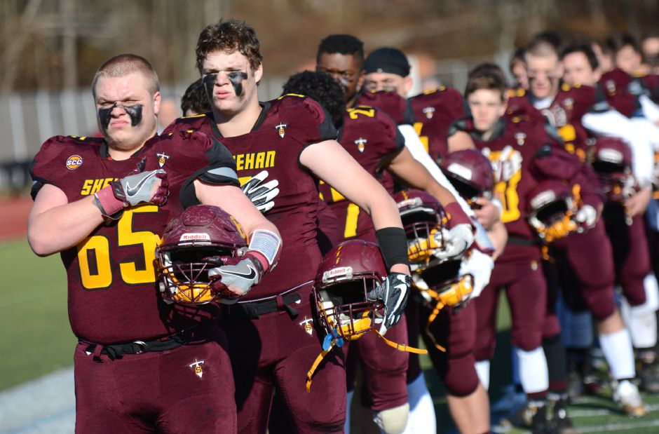 Members of the Sheehan football team during the national anthem prior to the team's annual Thanksgiving Day football game against Lyman Hall on Thursday, Nov. 23, 2017. The Titans defeated the Trojans, 49-20. | Bryan Lipiner, Record-Journal
