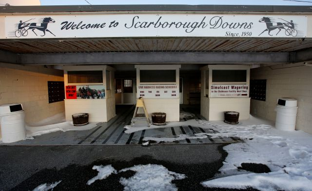 A sign welcomes race fans to the Scarborough Downs harness racing track, Wednesday, Jan. 10, 2018, in Scarborough, Maine. The track is one of two Maine suitors trying to lure Amazon to the Pine Tree State. (AP Photo/Robert F. Bukaty)