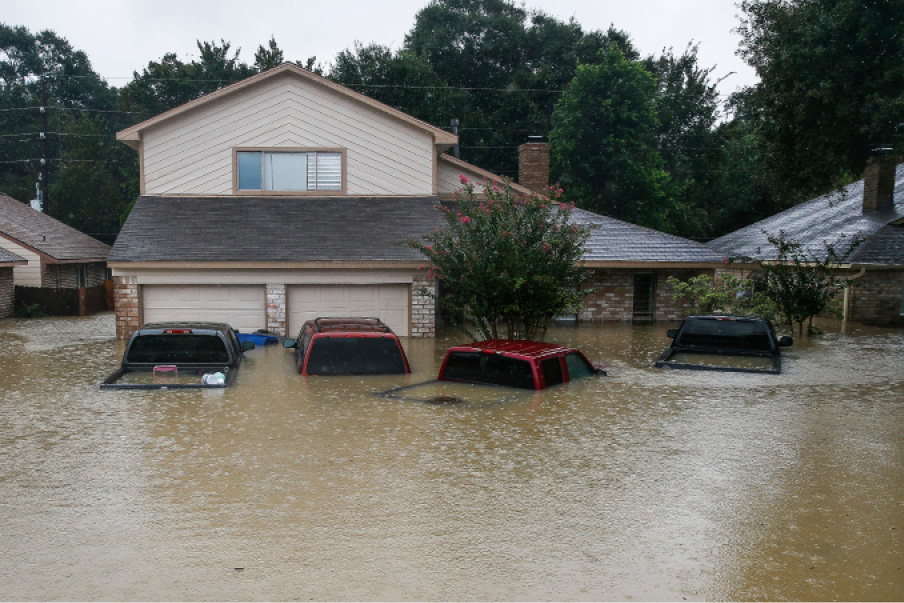 FILE - In this Aug. 29, 2017, file photo, trucks are submerged on Pine Cliff Drive in Houston during heavy rainfall from Tropical Storm Harvey. Few American cities depend on cars as much as Houston, and Harvey