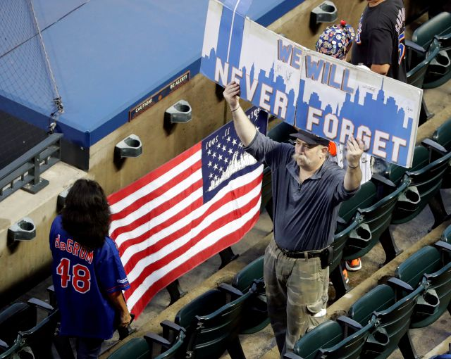 Fans hold up signs before the start of a baseball game between the New York Mets and the Miami Marlins, Tuesday, Sept. 11, 2018, in New York. (AP Photo/Frank Franklin II)